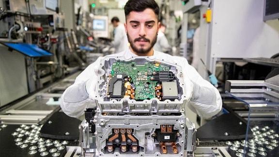 Ein Mitarbeiter bei Continental fügt in der Produktion der Leistungselektronik für Elektrofahrzeuge ein Wechselrichter und ein 12-Volt-Netzteil für das Fahrzeugbordnetz zusammen.