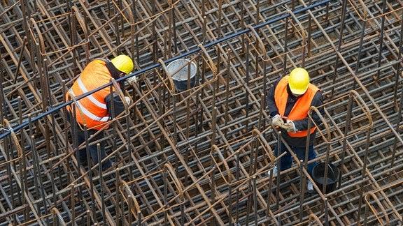 Bauarbeiter errichten auf einer Baustelle ein Stahlgeflecht
