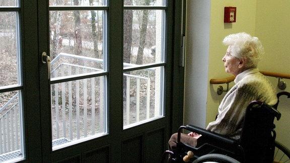 Eine Heimbewohnerin sitzt alleine am Fenster und schaut nach draussen.