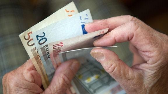 Eine ältere Frau zählt Geld.