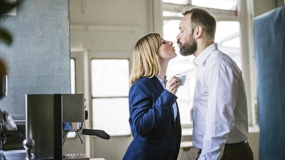 Zwei Menschen küssen sich am Arbeitsplatz