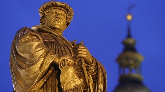 Blick auf das Denkmal des Reformators Martin Luther (1483-1546) und die Kirchturmspitze der St. Andreaskirche in Lutherstadt-Eisleben.