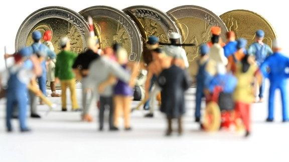 Figuren in Arbeitskleidung unterschiedlicher Branchen stehen vor Euro Geldmünzen im Wert von 8,50.