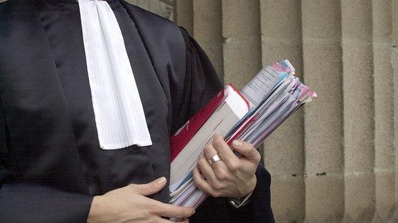 Eine Person in einer Richterrobe hält Akten und Gesetzbuch in der Hand