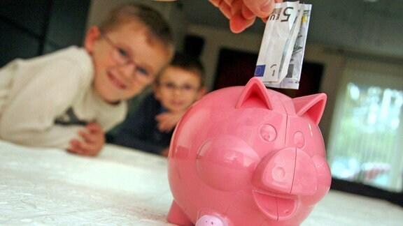 Zwei Jungs blicken auf ein pinkes Sparschwein, welches mit einem 5-Euro-Schein gefüttert wird
