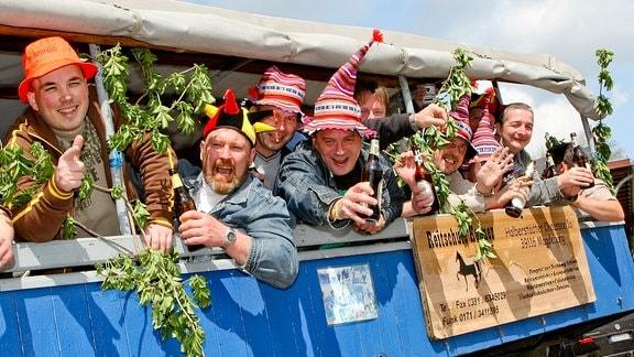 Eine Gruppe von Männern ist in Magdeburg mit einer Pferdekutsche unterwegs und feiert ausgelassen den Herrentag.