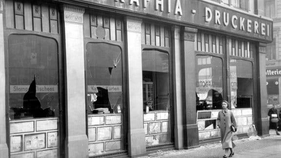 November 1938, eine Frau läuft an einer Druckerei mit kaputten Fensterscheiben vorbei.