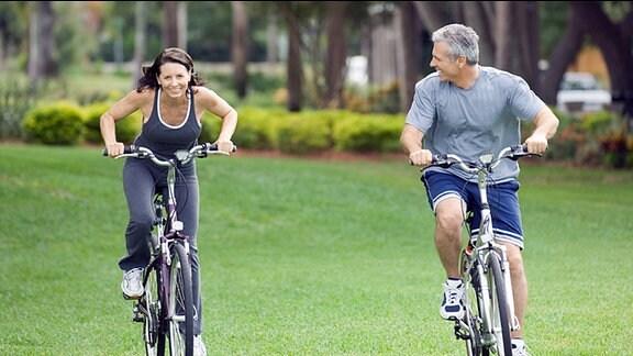 Ein Mann und eine Frau fahren in einem Park ohne Helm mit dem Fahrrad.