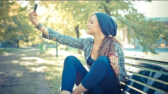 Eine junge Frau sitzt auf einer Parkbank und macht mit ihrem Smartphone ein Selfie