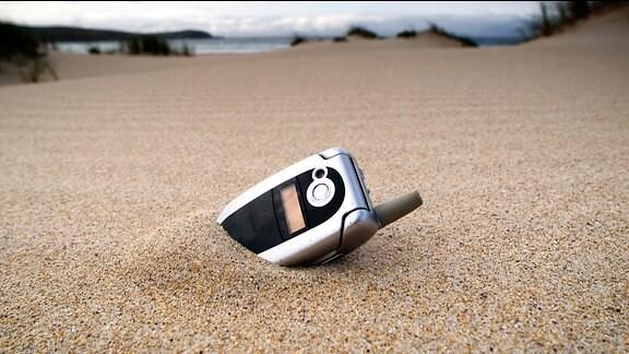 Ein Handy steckt Sand