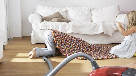 Ein Junge versteckt sich unter einem Teppich, ein Mädchen fotografiert