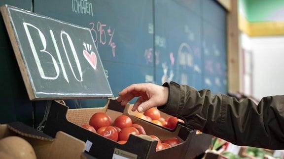 Ein Mann greift nach Bio-Tomaten in einer Gemüsauslage