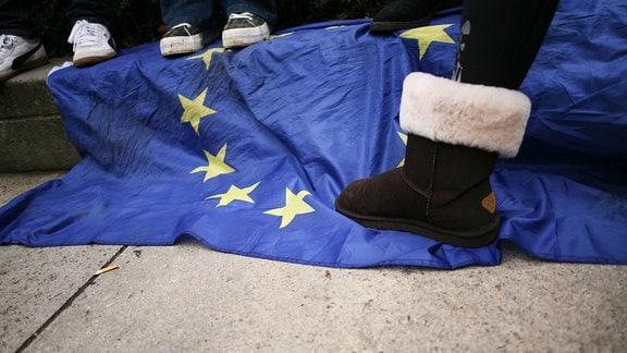 Ein Brexit-Befürworter steht mit dem Fuß auf einem Stern einer EU-Flagge