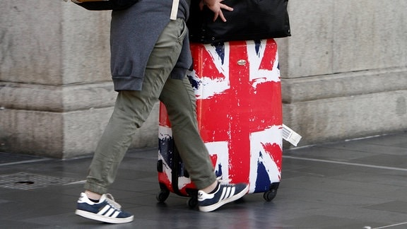 Bahnreisende mit einem Rollkoffer in den Farben der Flagge Großbrittaniens
