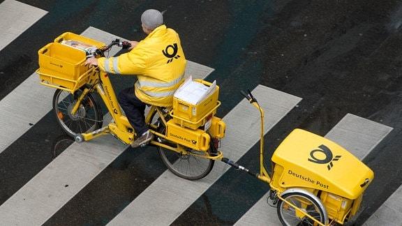 Ein Briefträger der Deutschen Post fährt mit einem Fahrrad über einen Zebrastreifen.