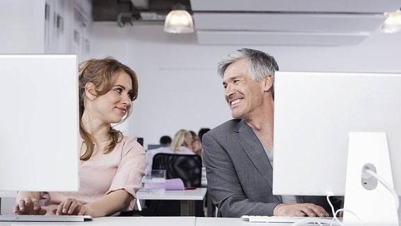 Kollegen im Büro hinter Computerbildschirmen