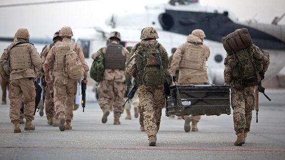 Bundeswehrsoldaten tragen auf dem Flughafen in Masar-i-Scharif eine Feldkiste zu einem wartenden Hubschrauber