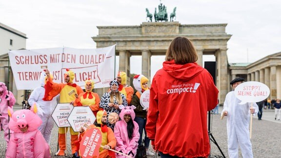 Aktivisten der Bürgerbewegung Campact protestieren am Brandenburger Tor in Berlin gegen das Tierwohl-Label