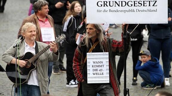 Liedermacher Gottfried Gunther Grimmer, rechts ein Demonstrant mit einem Schild 'Grundgesetz und Wann kommt die 47. Welle'