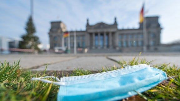 Ein Mund-Nasen-Schutz liegt auf der Wiese vor dem Deutschen Bundestag Berlin.
