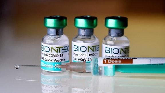 Drei Ampullen mit Impfstoff, davor eine Spritze
