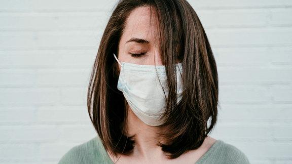 Frau hält Augen geschlossen und trägt Mund-Nasen-Schutz