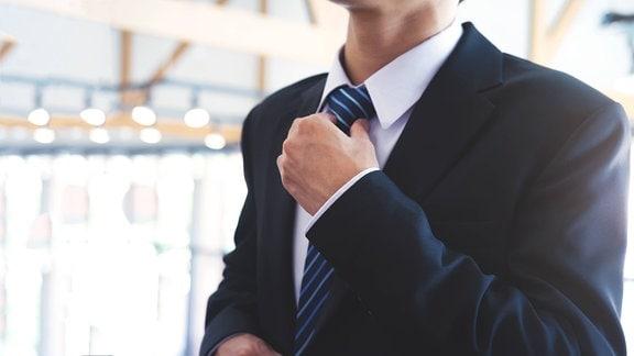 Ein Mann bindet sich die Krawatte