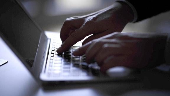 Im Halbdunkel wird die Tastatur eines Laptops bedient.