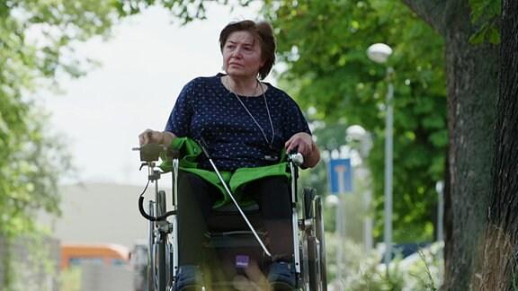 Eine Frau fährt im Rollstuhl durch eine Straße.