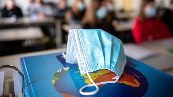 Ein Mund- und Nasentschutz liegt im Unterricht auf einem Weltatlas.