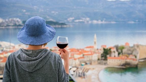 Eine Frau von hinten mit einem Glas Rotwein