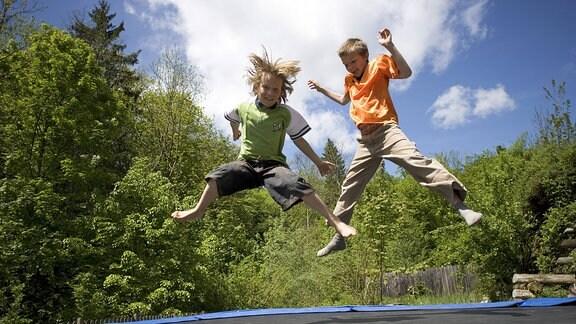 Zwei Jungs springen auf einem Trampolin