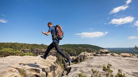 ein Wanderer springt über eine Felsspalte auf der Wenzelwand am Reitsteig