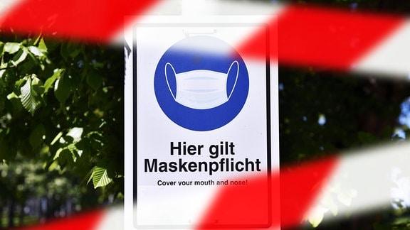 FOTOMONTAGE, Maskenpflicht-Schild hinter Absperrband
