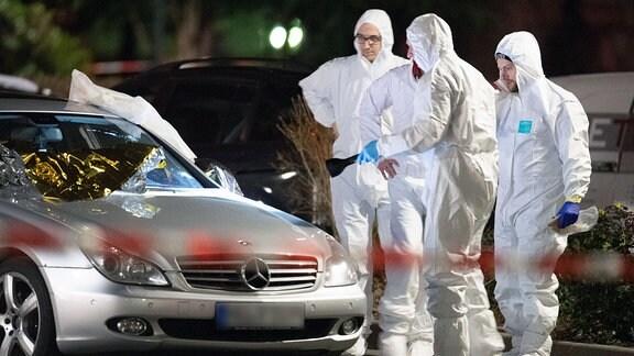 Forensiker arbeiten an einem Tatort in Hanau-Kesselstadt an einem Mercedes.