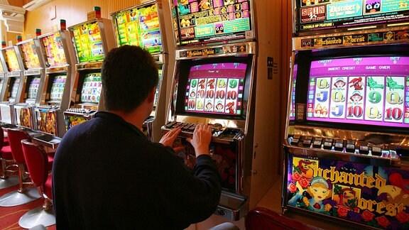 Ein Gast sitzt im Spielcasino in Bad Homburg an einem einarmigen Banditen und hofft den Jackpot zu knacken.