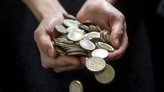 Eine Frau hält zahlreiche Münzen in den Händen und lässt diese auf den Boden fallen.