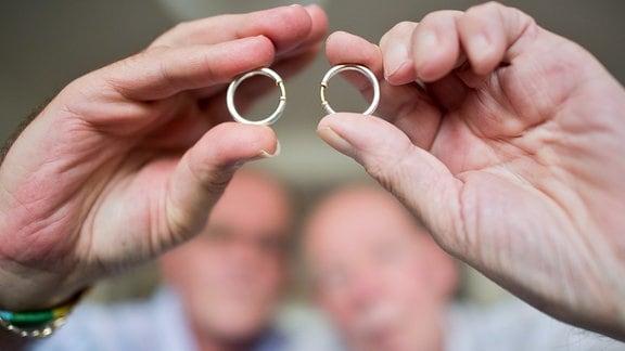 Ein homosexuelles Paar zeigt seine Eheringe.