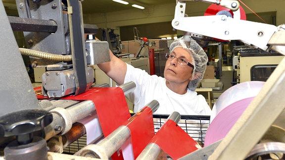 Eine Frau arbeitet bei einem Backwarenhersteller an einer Maschine