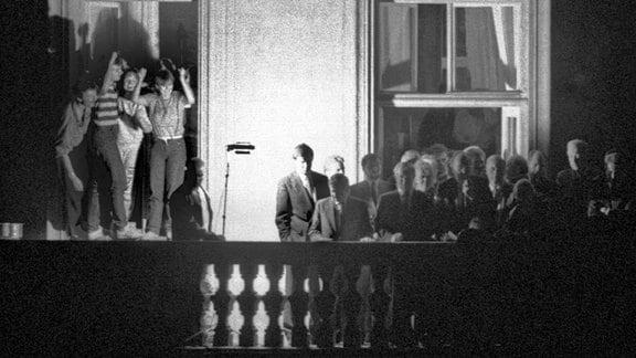 Der damalige Außenminister Hans-Dietrich Genscher (unter dem Fensterkreuz rechts) steht am 30.09.1989 mit anderen Politikern auf dem Balkon der bundesdeutschen Botschaft in Prag.