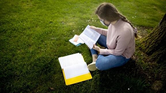 Junge Studentin sitzt an einem Baum im Freien und lernt.