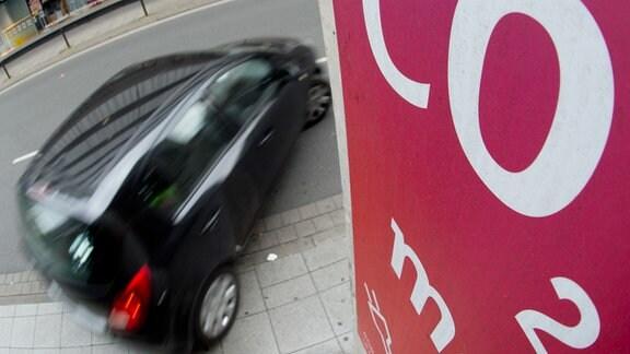 """Ein Auto fährt an einem Schild mit Aufschrift """"CO2"""" vorbei."""