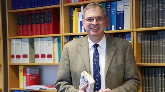 Prof. Dr. Jochen Rozek hält vor einem Bücherregal das Gesetzbuch über Ausländerrecht in Händen.