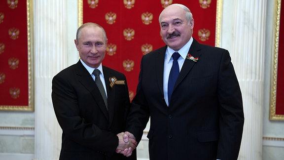 Der russische Präsident Wladimir Putin und Belarus Präsident Alexander Lukashenko geben sich die Hand. Putin hatte ihn für den 24. Juni 2020 nach Moskau zur Siegesparade eingeladen