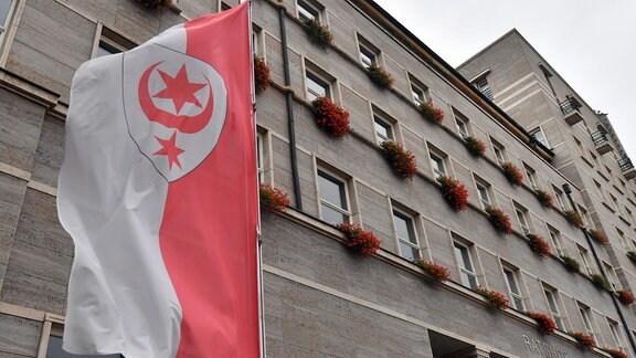 Rathaus in Halle 2019, im Vordergrund ist eine Flagge mit dem Stadtwappen.