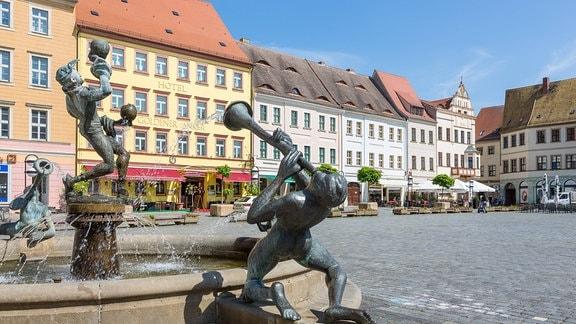Brunnen auf dem Torgauer Marktplatz, dahinter das Hotel Goldener Anker.