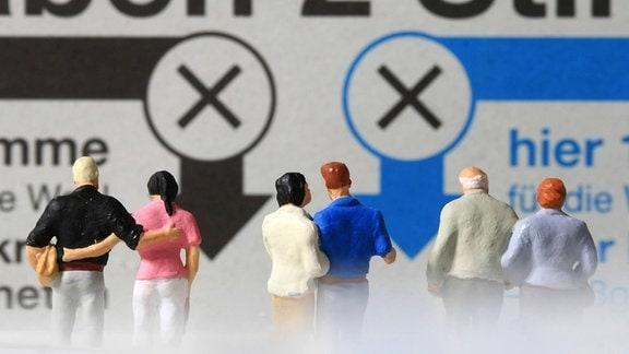 Kleine Figuren stehen auf einem Stimmzettel