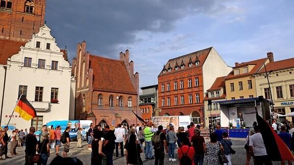 Teilnehmer stehen während einer Wahlkampfkundgebung der AfD Sachsen-Anhalt in Stendal auf dem Marktplatz und hören Martin Reichardt, Landesvorsitzenden der AfD Sachsen-Anhalt, zu.