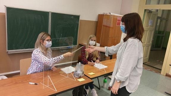 Drei Frauen arbeiten in einem Wahllokal. Einer wird ein Wahlschein überreicht.