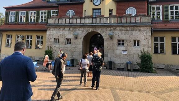 Menschen stehen an vor der Pestalozzischule in Weimar
